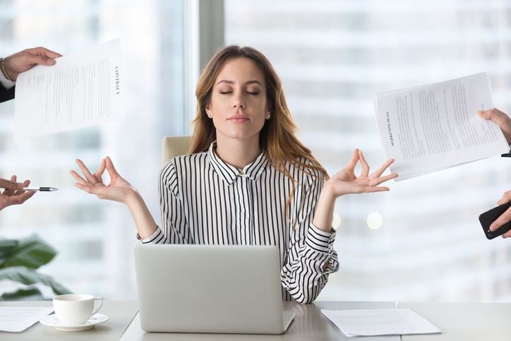 Female tax professional meditating during stressful tax season to avoid burnout.