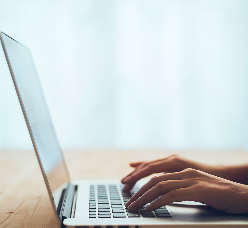 Photo of open laptop with hands of woman typing on keyboard