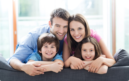 Photo of man and woman smiling above their son and daughter on a couch