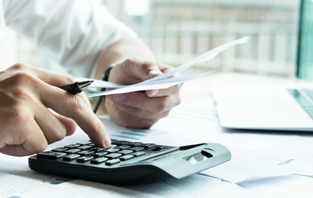 Photo of businessman hands holding stack of papers and typing on calculator