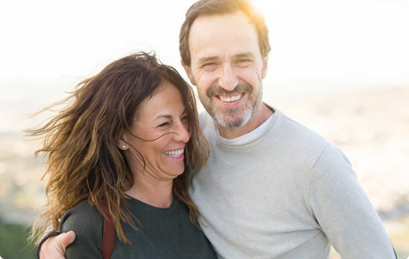 Photo of smiling man with arm around smiling woman