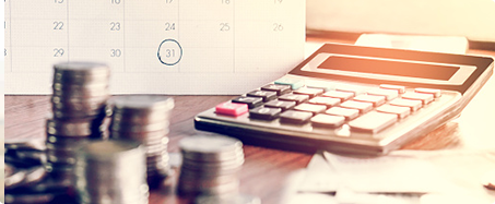 Photo of desk with calendar, calculator, and stacks of coins