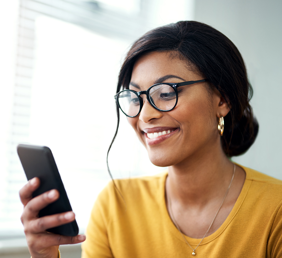Photo of smiling woman reading smartphone