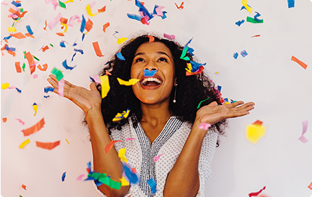 Photo of woman smiling surrounded by confetti