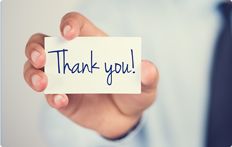 Photo of hand holding card with Thank You written on it