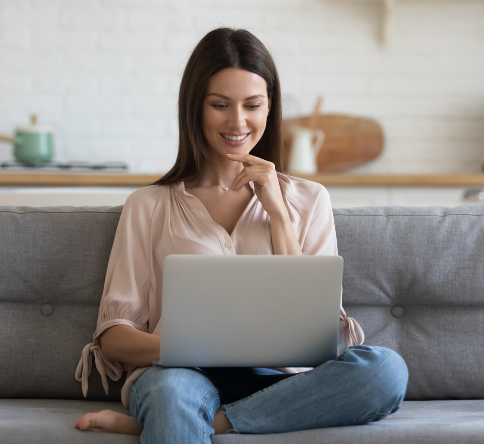 Photo of woman on couch smiling and looking at laptop